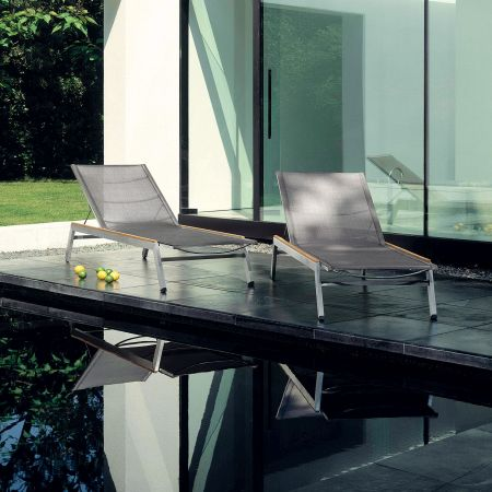 A Pair Of Barlow Tyrie Equinox Chaises Shown With Teak Caps Poolside.