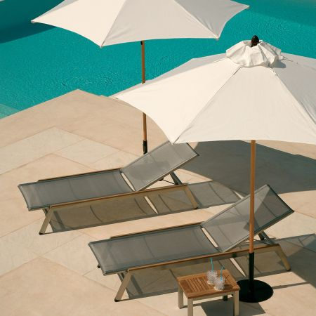 A Pair Of Barlow Tyrie Equinox Chaises Shown With Umbrellas And Base Along With A Chaise Side Table.A Pair Of Barlow Tyrie Equinox Chaises Shown With Umbrellas And Base Along With A Chaise Side Table.
